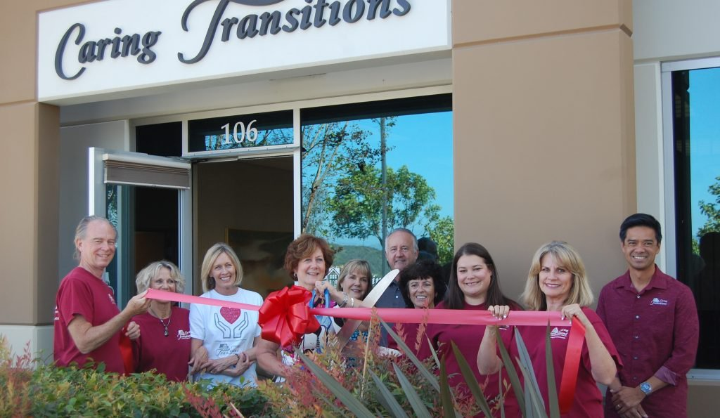 Caring Transitions Team cutting a ribbon
